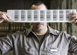 A warehouse worker holding up a sheet of bar code shipping lables in a distribution warehouse.