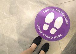 purple-social-distancing-sign-on-the-floor-DBL6TMR